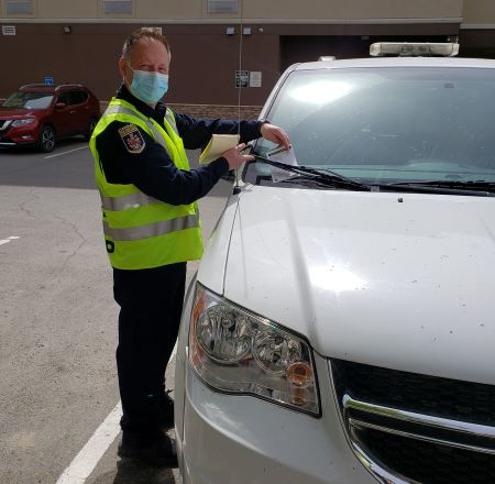 Sandro Piroddi, Kamloops Community Services Support Liaison. A man in a high visible yellow vest, blue non-medical mask, dark blue shirt with 'Crime Prevention' shoulder patch and dark pants, places a paper notice under the windshield wiper of a white van in a parking lot.